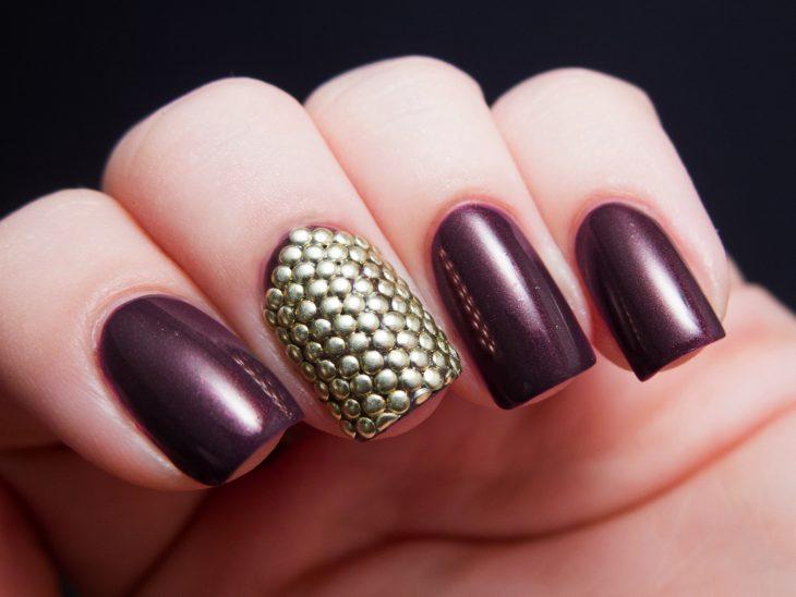 Diseños de uñas color ciruela con brillos de color dorado
