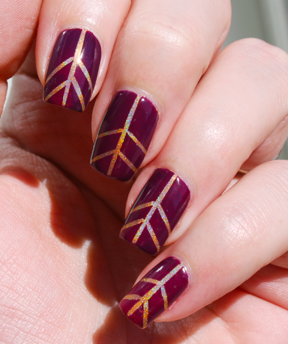 Uñas de color ciruela con lineas de color dorado