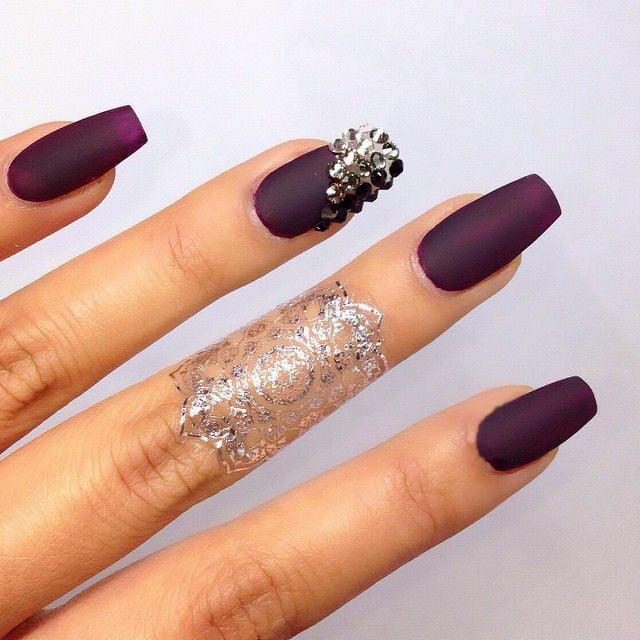 Uñas de color ciruela con piedras de color gris