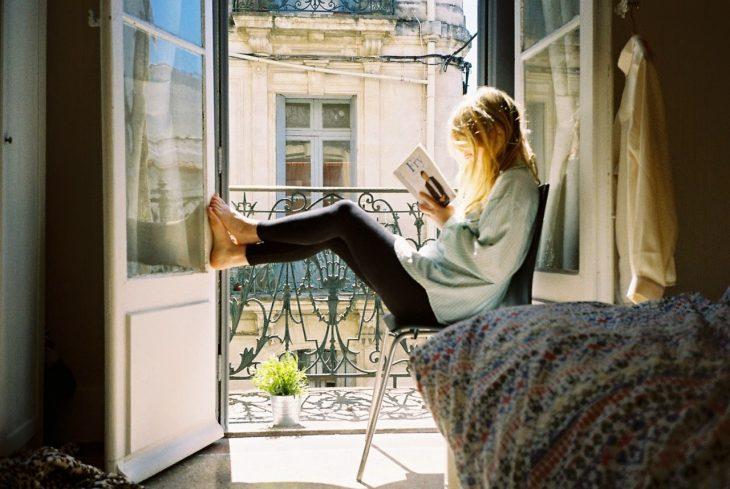 Chica sentada junto a una ventana leyendo un libro