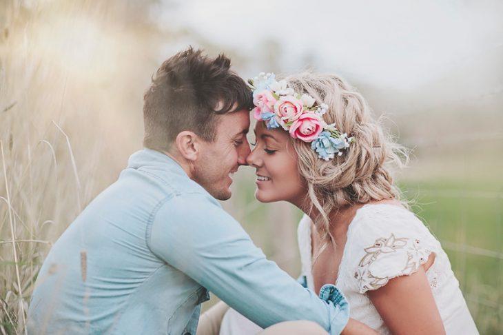 Pareja de novios sentados en el pasto besándose
