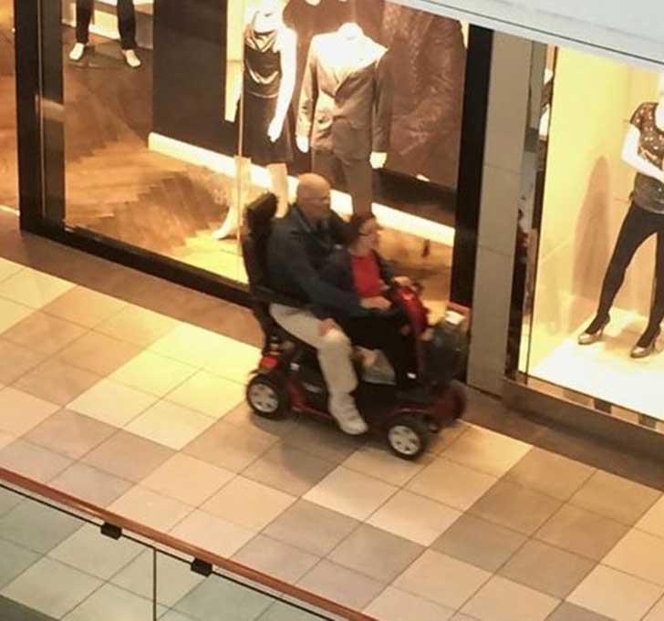 pareja de viejitos en una silla de ruedas motorizada