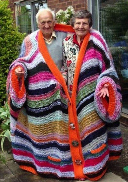 Pareja con un suéter inmenso tejido