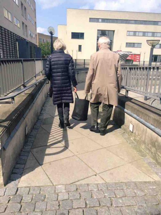 Pareja de ancianos cargando una bolsa entre los dos