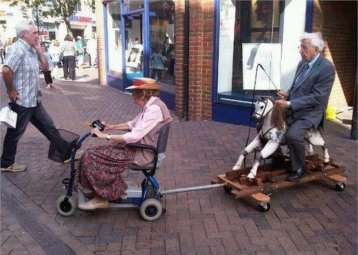 Viejitos divirtiéndose en silla de ruedas y un caballito
