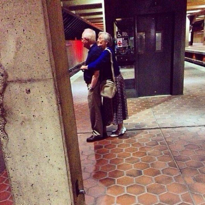 Pareja de ancianos abrazados esperando el tren