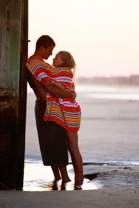 Pareja de novios abrazados mientras están en la playa disfrutando del atardecer