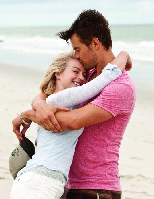 Pareja de novios abrazados mientras están parados junto al mar