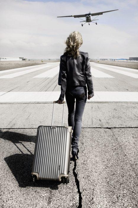 Chica caminando por una pista con una maleta en la mano