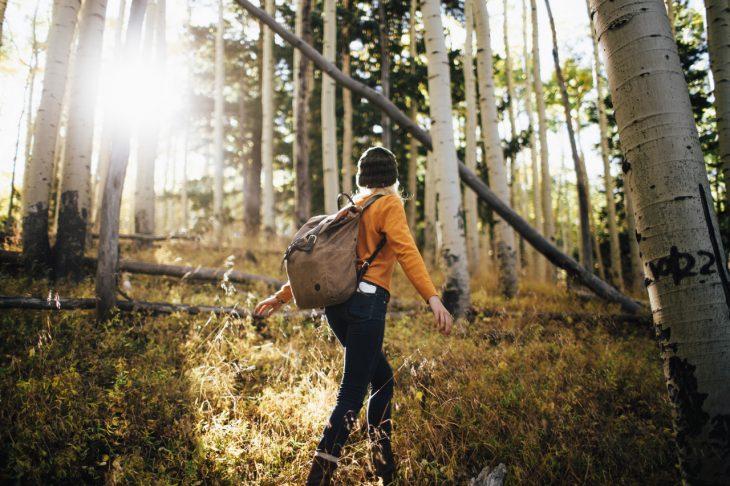 Chica caminando por el bosque