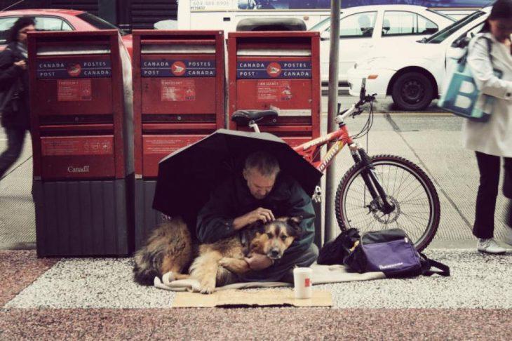 Hombre sin hogar junto a su perro