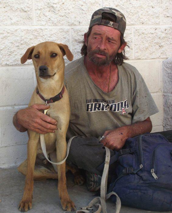 Hombre sin dinero abrazando a su perro
