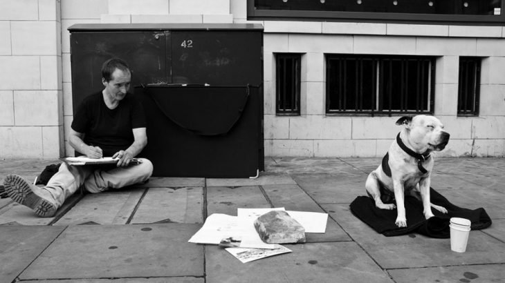 Hombre sin hogar pintando un perro