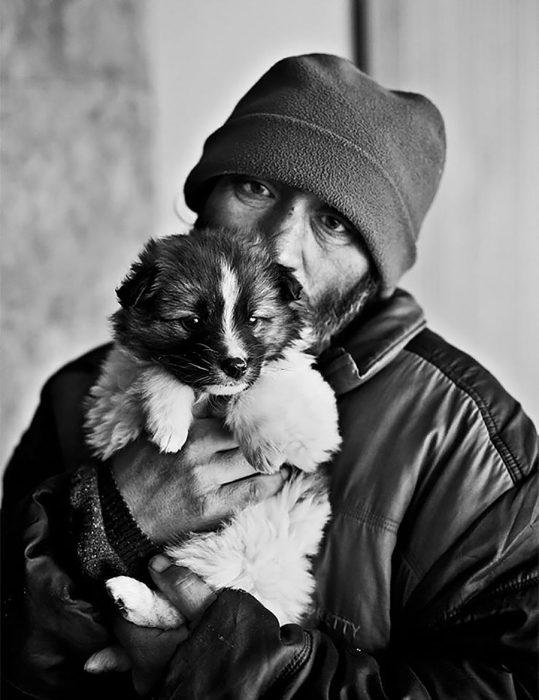 Persona sin hogar con su pequeño cachorro