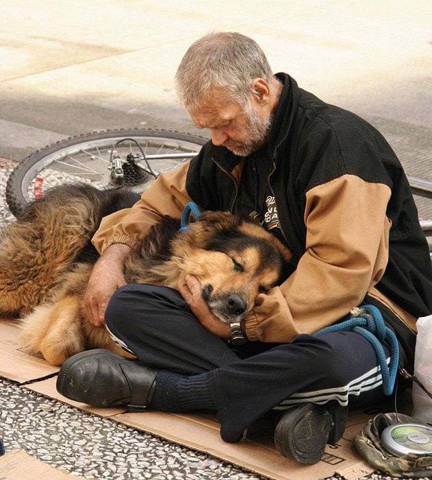 Anciano indigente abrazando a su perro