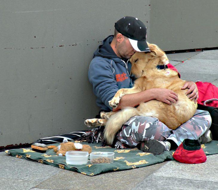 Chico sin hogar abrazando a su perro