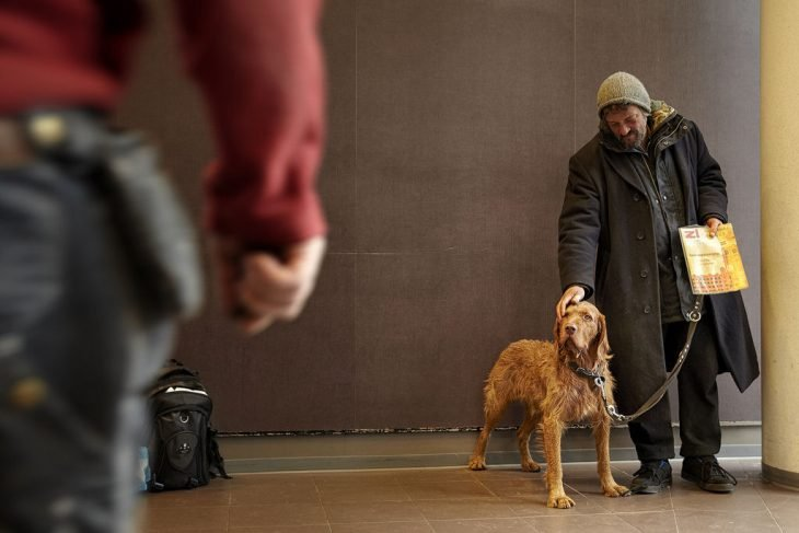 Persona sin hogar acariciando a su perro