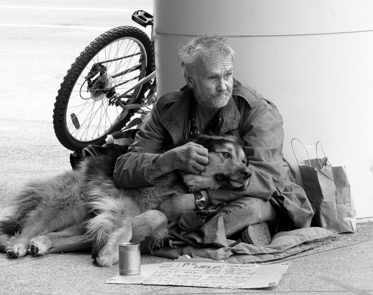 Hombre sin hogar abrazando a su perro