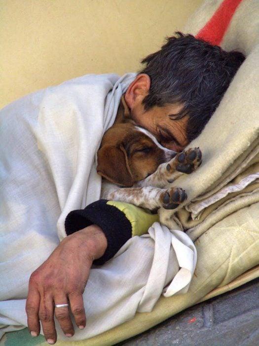Hombre dormido en la calle junto a su cachorro