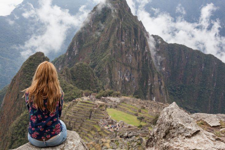 Chica sentada en una montaña reflexionando