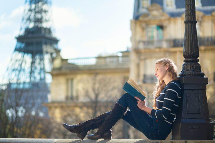 Chica recargada en un poste leyendo
