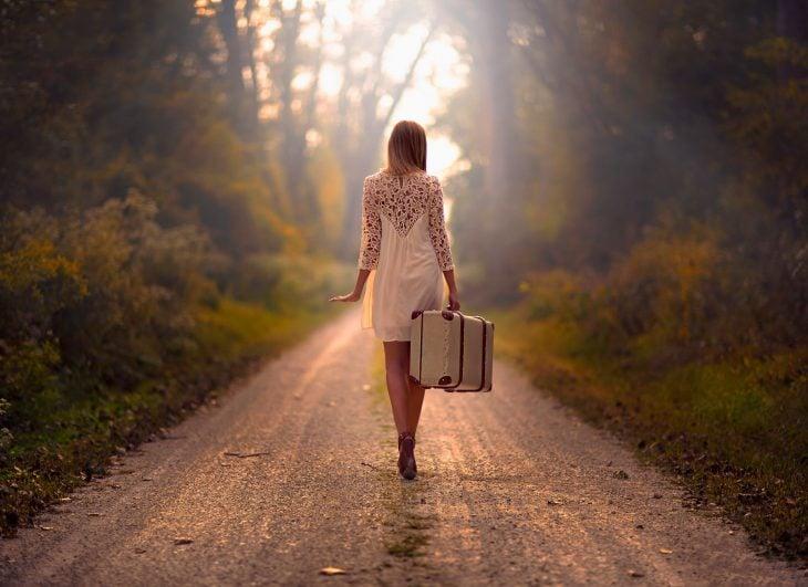 Chica a mitad de la carretera con una maleta