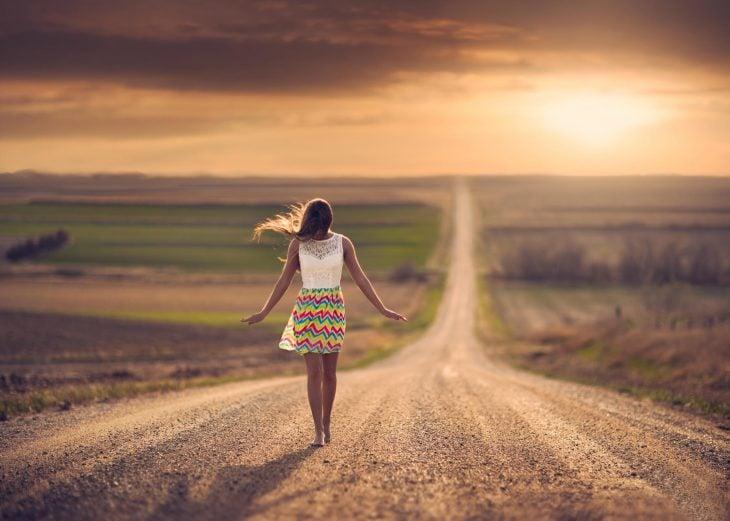 Chica caminando por la carretera