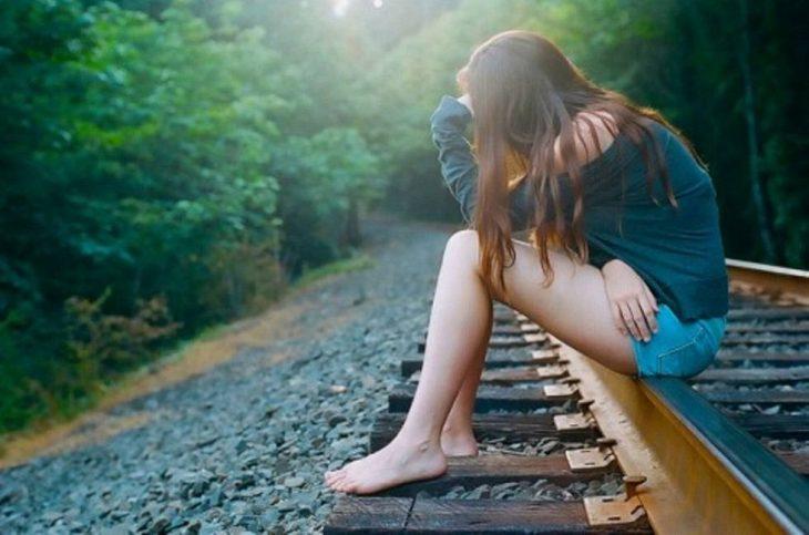 Chica sentada sobre las vías del tren tomándose la cabeza y pensando