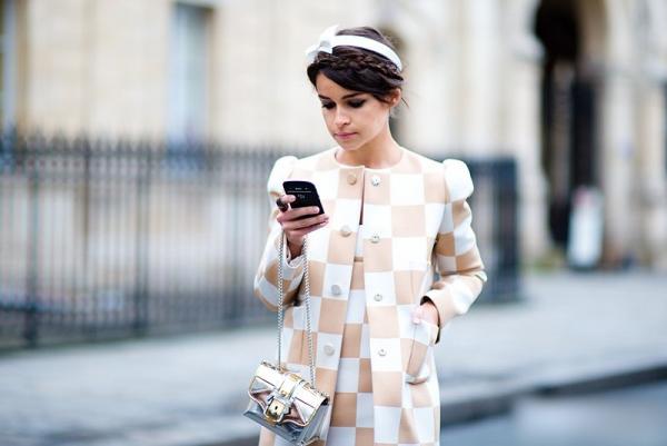 Chica parada en la calle enviando mensajes de texto