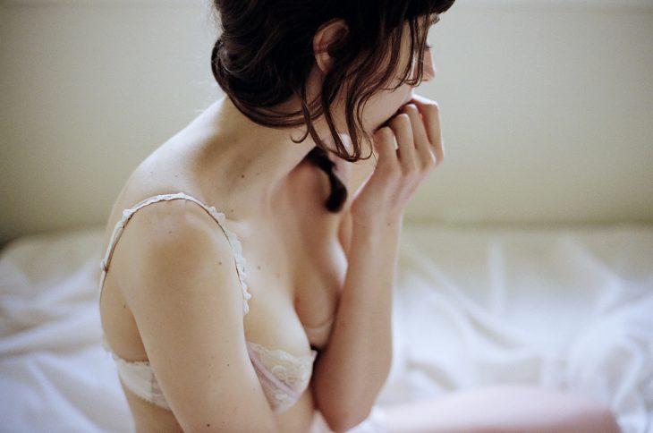 Chica mordiendo sus uñas mientras está sentada en la cama