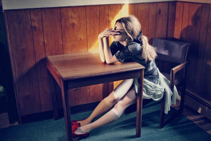 Chica sentada frente a una mesa pensando