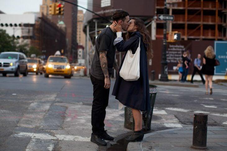 Pareja dándose un beso en la calle