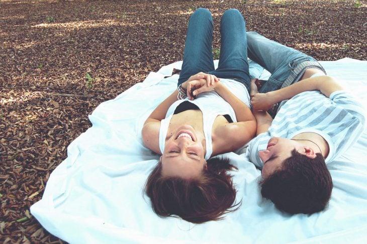 Amigos acostados en un parque riendo