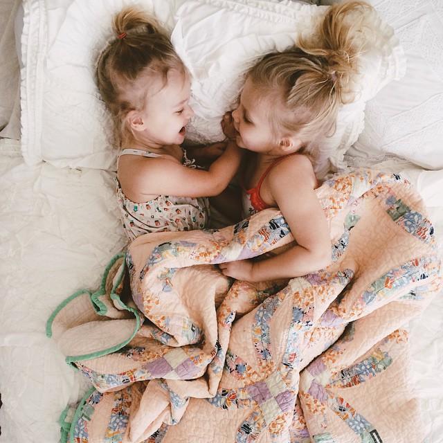 Niñas pequeñas platicando acostadas en la cama