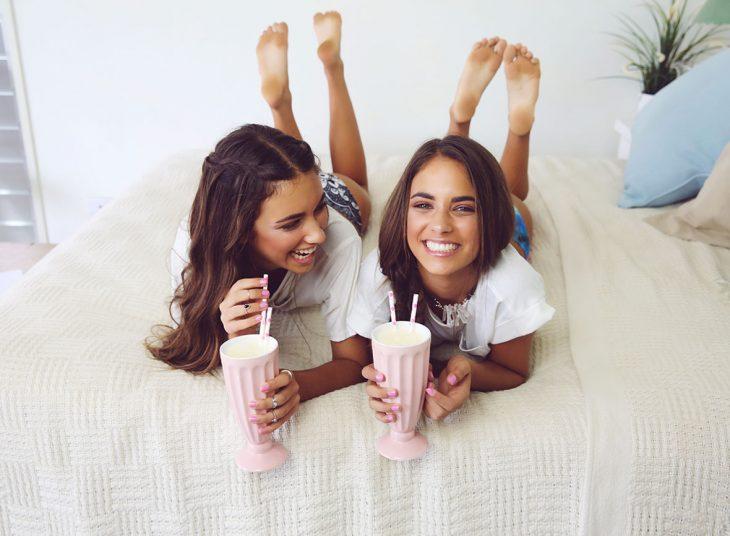 Chicas acostadas en la cama tomando malteada