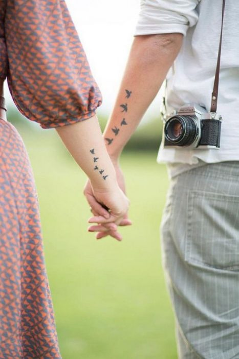 pareja tomados de las manos mostrando sus tatuajes de pájaros