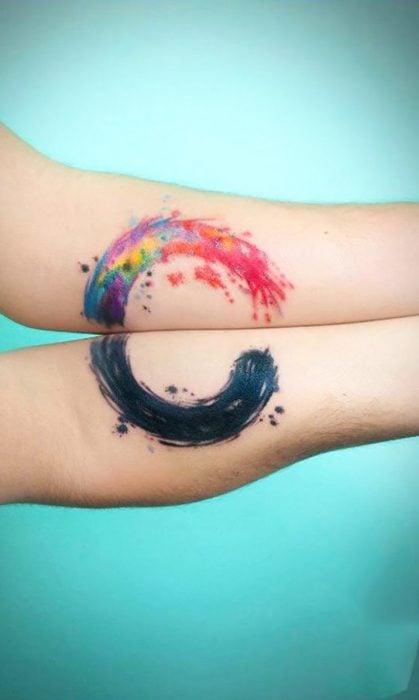 pareja mostrando sus tatuajes en forma de circulo