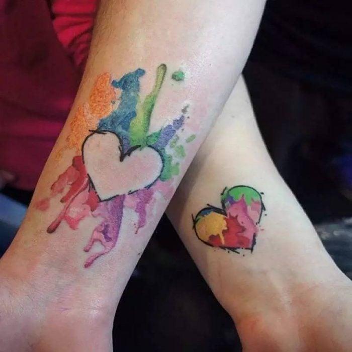 Pareja mostrando sus tatuajes en las manos