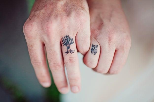 pareja tomados de las manos mostrando sus tatuajes de árbol y buho