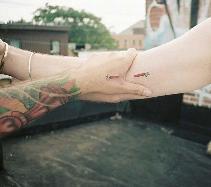 pareja tomados de las manos mostrando sus tatuajes de dinamita