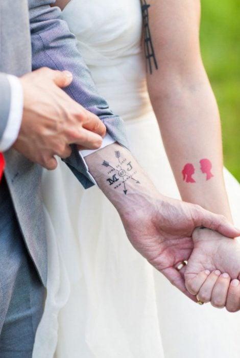 Pareja mostrando sus tatuajes de boda
