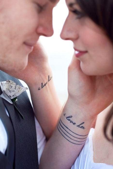 pareja tomandose la cara mostrando sus tatuajes en las manos