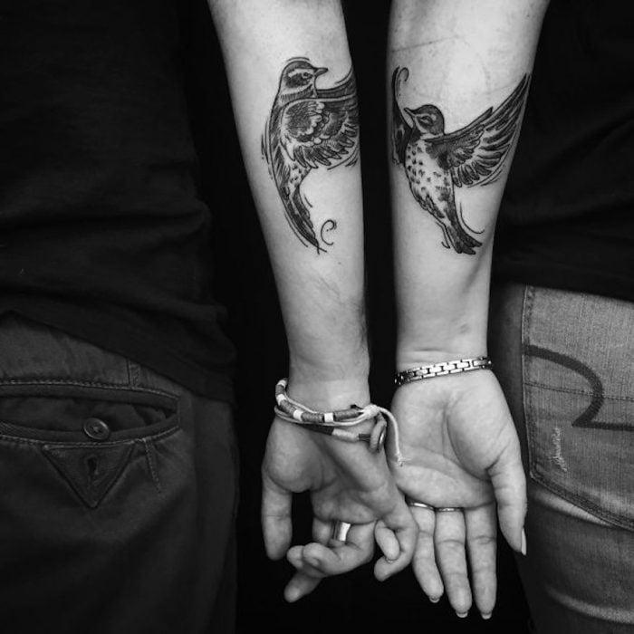 pareja mostrando sus tatuajes en el antebrazo de unas golondrinas