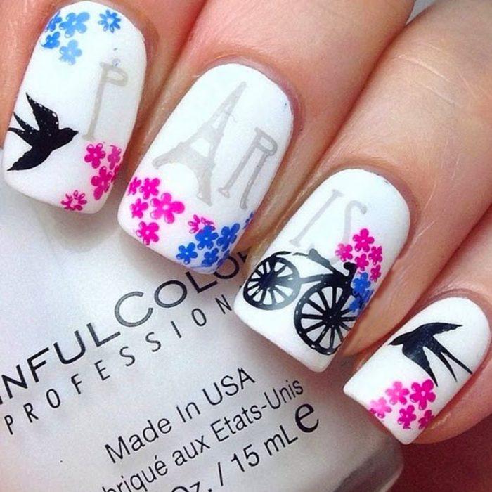 Estilo de uñas parisino en color blanco con una bicicleta