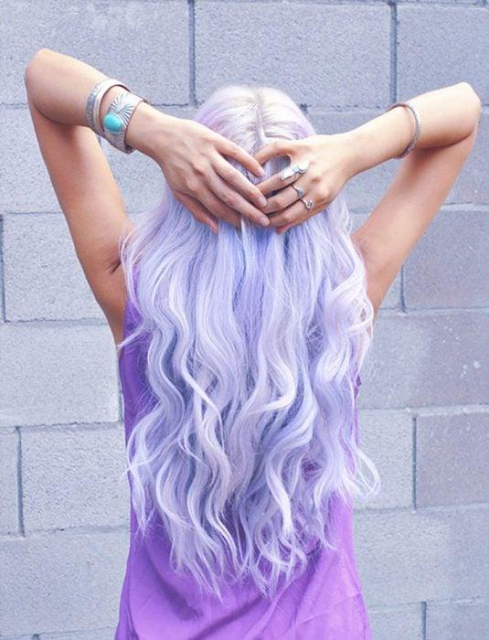 Chica con el cabello de color lila sosteniéndose la cabeza