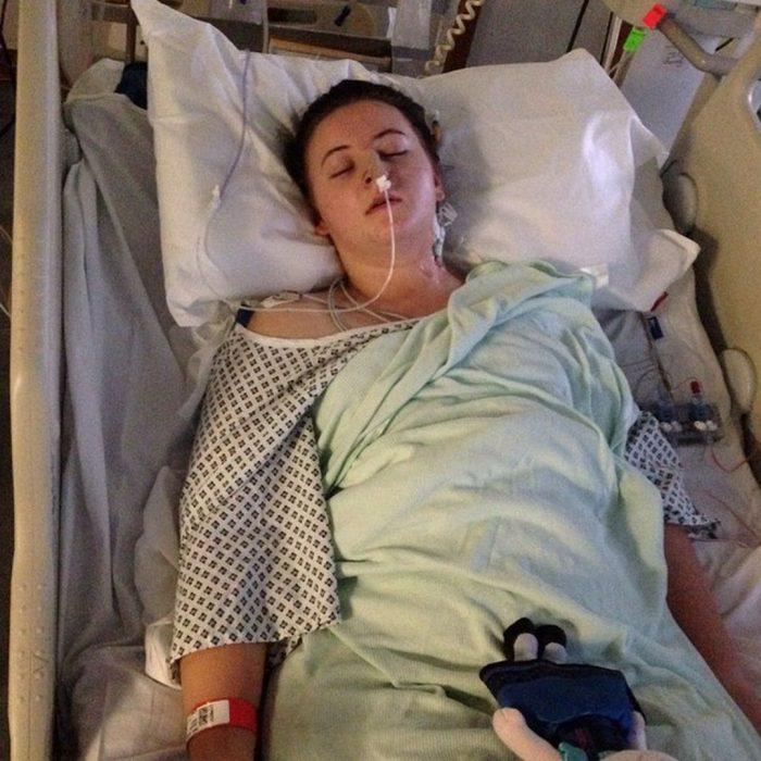 Chica recostada en una cama de hospital enferma