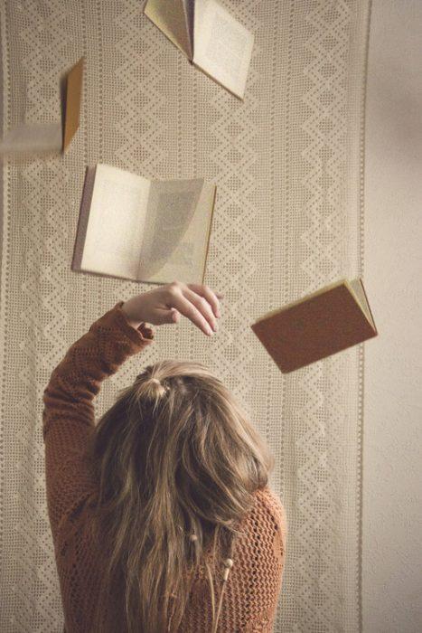chica aventando libros hacia arriba