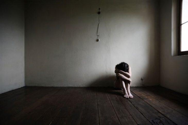 chica sola en habitación vacía