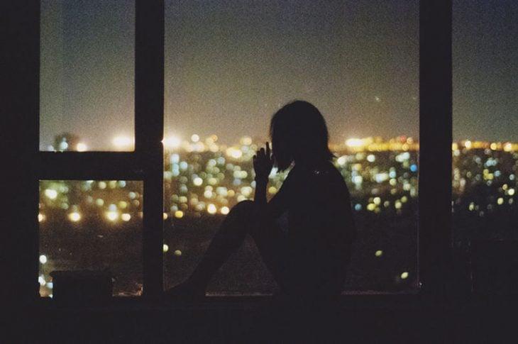 chica mirando fuera de la ventana de noche