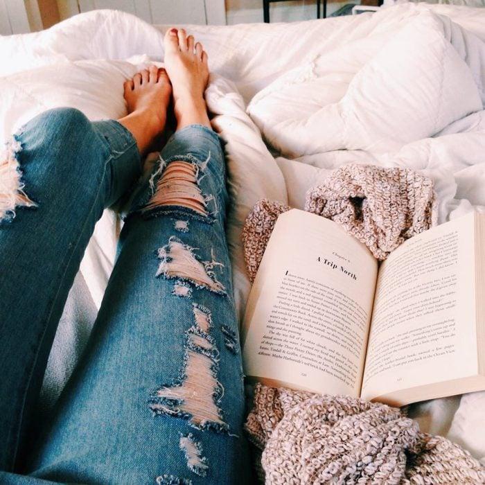 chica acostada en cama con un libro a un lado
